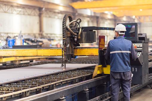 Steel worker on CNC plasma cutter machine 1164593906
