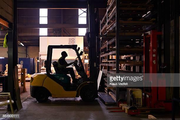 Steel worker operating forklift inside factory