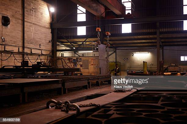 Steel worker operating huge crane at factory