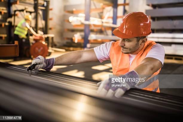 trabalhador de aço a medição enquanto estiver trabalhando com metal na fábrica de alumínio. - capacete de trabalho - fotografias e filmes do acervo