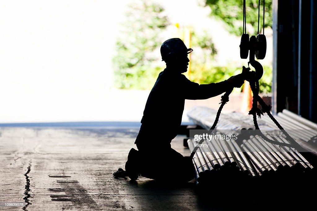 Steel worker tying metal tubes to crane jib in warehouse : Stock Photo