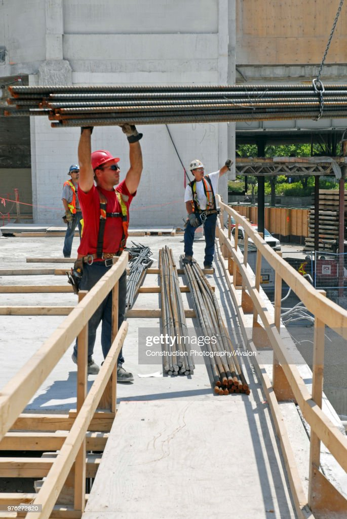 steel worker, with load of rebar, PCL Contractors