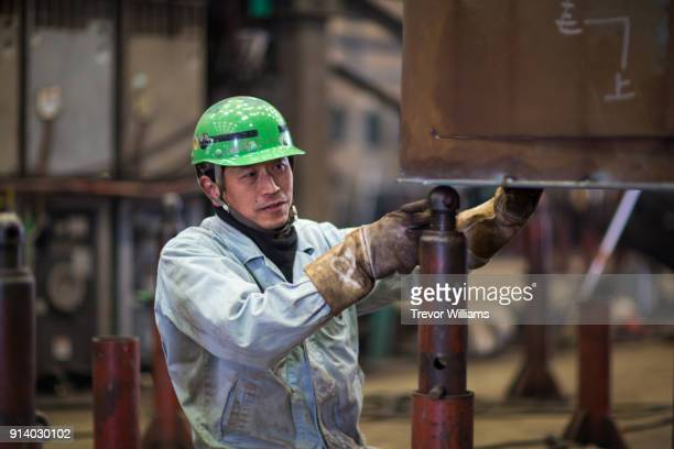 a steel worker working in a shipbuilding factory - ジャンプスーツ ストックフォトと画像
