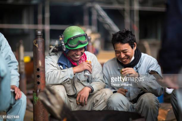 Steel workers gathering and laughing during a break from work at a shipbuilding factory