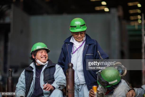 steel workers gathering and laughing during a break from work at a shipbuilding factory - ジャンプスーツ ストックフォトと画像