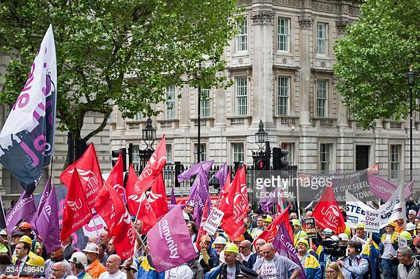 Steel workers hold placards and wave banners as they pass Downing Street during a protest march through central London on May 25 2016 Britain's...