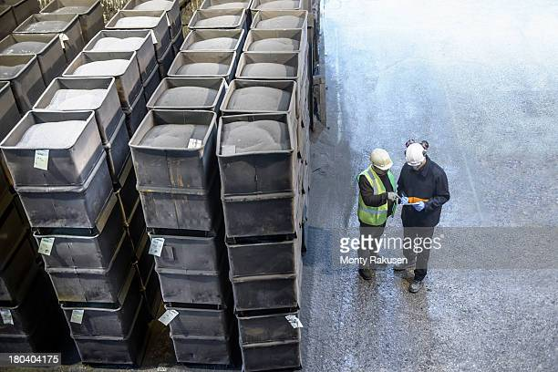 steel workers in industrial steel foundry inspecting paperwork next to crates of steel shot, high angle view - west midlands stock pictures, royalty-free photos & images