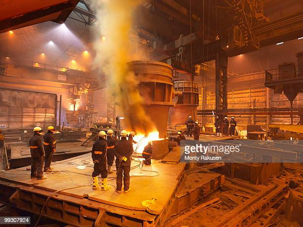 steel workers in plant working on ladle - steelmaking stock photos and pictures