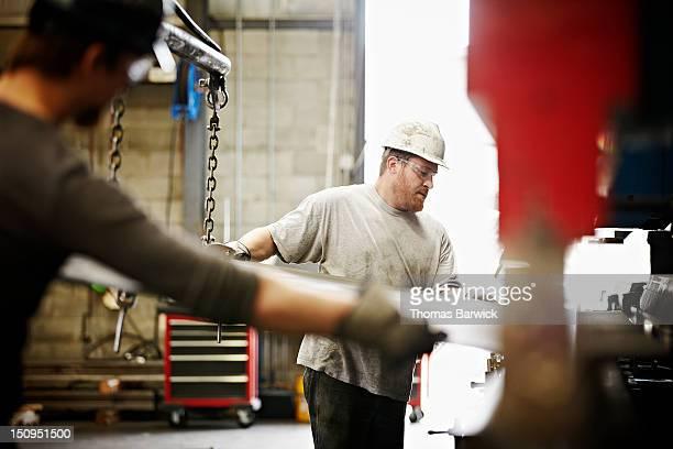Steel workers placing steel in brake press