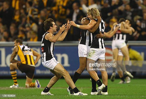 Steele Sidebottom Harry O'Brien and Dale Thomas of the Magpies celebrate winning the first preliminary final match between the Collingwood Magpies...