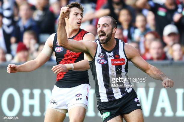 Steele Sidebottom of the Magpies celebrates a goal past Andrew MGrath of the Bombers during the round five AFL match between the Collingwood Magpies...
