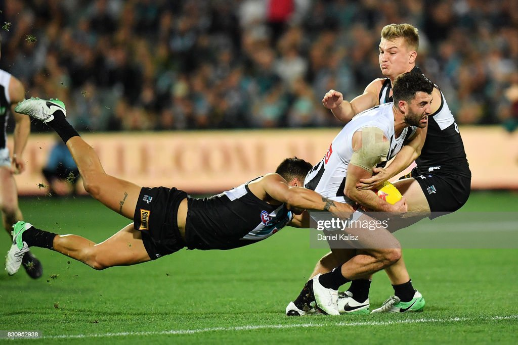 Steele Sidebottom of the Magpies is tackled by Ollie Wines and Jarman Impey of the Power during the round 21 AFL match between Port Adelaide Power and the Collingwood Magpies at Adelaide Oval on August 13, 2017 in Adelaide, Australia.