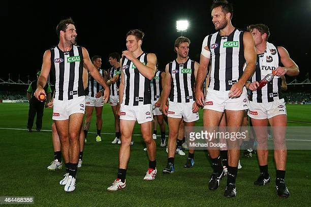 Steele Sidebottom of the Magpies Josh Kennedy and Nathan Brown walk off after their win during the NAB Challenge AFL match between Hawthorn Hawks and...