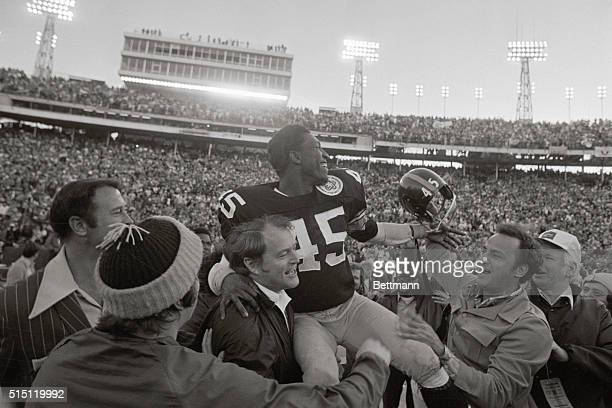 Steelers coach Chuck Noll hoists Jim Allen up and off the field as the Super Bowl X winners head for the locker room