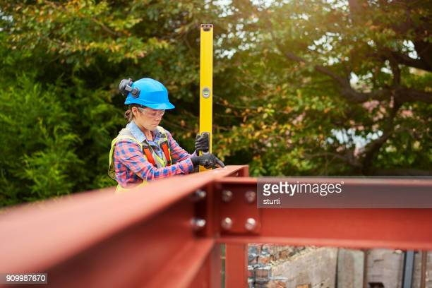 steelworker checking the levels - tighten stock photos and pictures