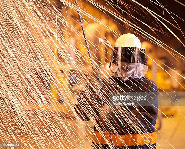 Steelworker holding sample lance behind sparks in steelworks