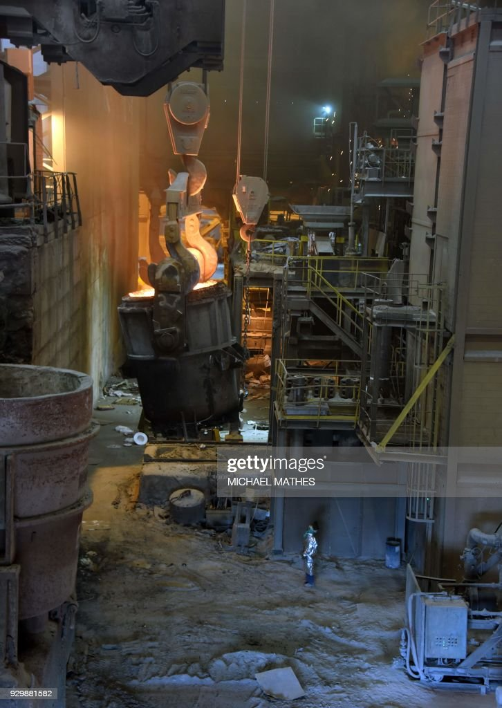 A steelworker in a protective suit works near a furnace at