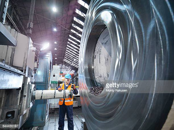 Steelworker inspecting cutting tool in engineering factory