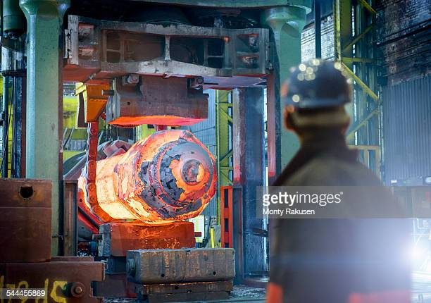 steelworker inspects hot steel in forging press in steelworks - sheffield stock pictures, royalty-free photos & images