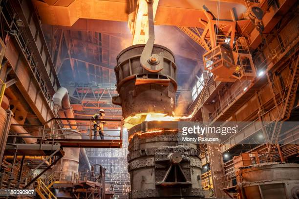 steelworker starting molten steel pour in steelworks - metal industry stock pictures, royalty-free photos & images