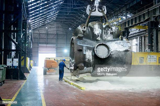 Steelworker sweeps sand from large casting