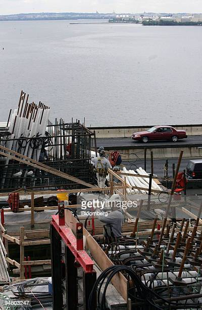 Steelworker tapes flexible reinforcement cables on a support structure of the Inner Loop of the new Woodrow Wilson Bridge as cars speed by on the...