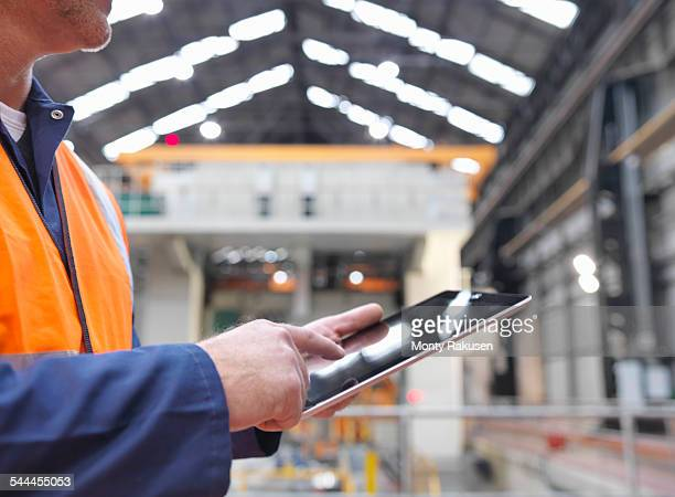 Steelworker using digital tablet in engineering factory, close up