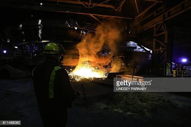 A steelworker watches as molten steel pours from one of the Blast Furnaces during 'tapping' at the British Steel Scunthorpe plant in north...
