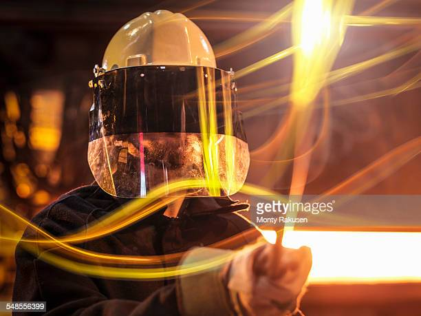 Steelworker with molten metal sample taken from furnace, close up