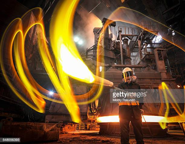 Steelworker with molten metal sample taken from furnace