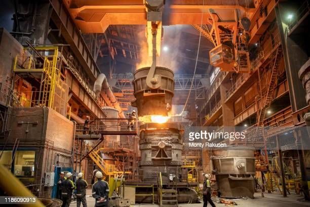 steelworkers looking on during steel pour in steelworks - fire natural phenomenon stock pictures, royalty-free photos & images