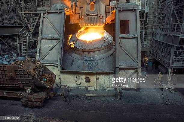 Steelworkers stand near a rail car filled with scrap iron in front of a furnace at the ArcelorMittal steelmaking factory in Kryvyi Rih Ukraine on...
