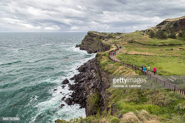 steep cliff next to songaksan mountain on jeju island - jeju stock photos and pictures