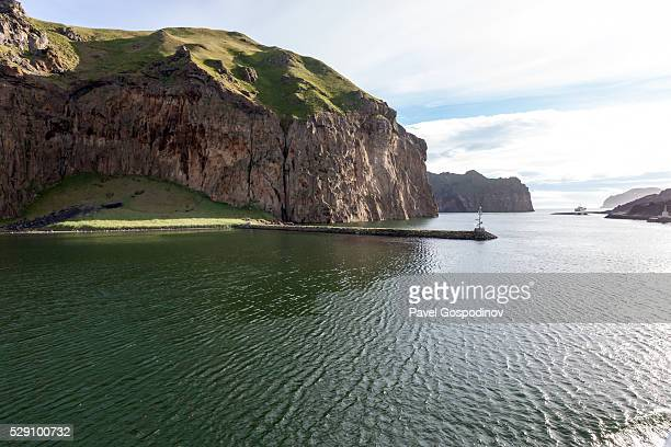 Steep cliffs and a small pier at the entrance of Vestmannaeyjar harbour, Westman Islands archipelago