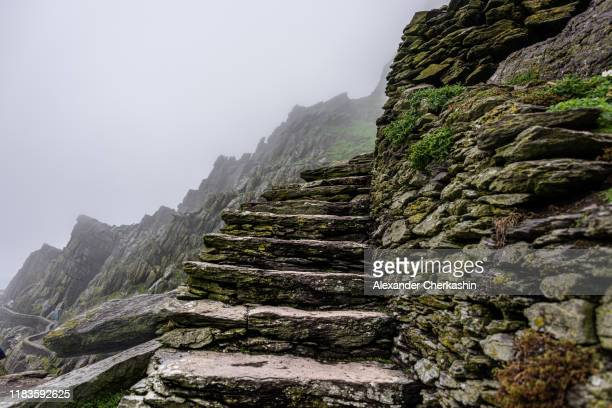 steep stone steps on the edge of ancient trail with ragged cliffs in the background in the dense fog. - skellig michael ストックフォトと画像