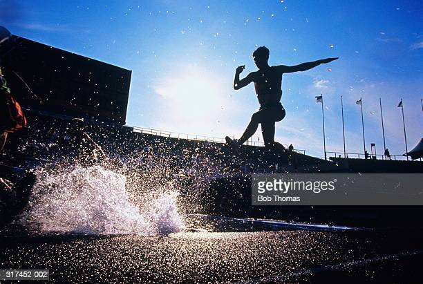 steeple chase runner about to land in water, silhouette, low view - track and field stadium stock pictures, royalty-free photos & images