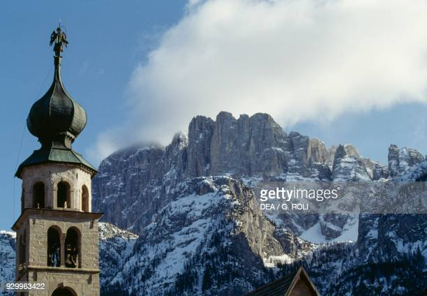 Steeple of the Church of St Thomas the Apostle in San Tomaso Agordino with the peak of Mount Civetta in the background Dolomites Veneto Italy