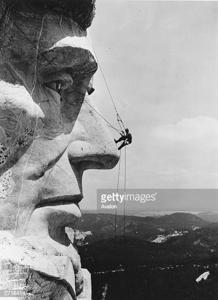 Steeplejack Mike O'Meara suspended on ropes on the tip of Abraham Lincoln's nose for the biannual cleaning of the Mount Rushmore National Memorial...