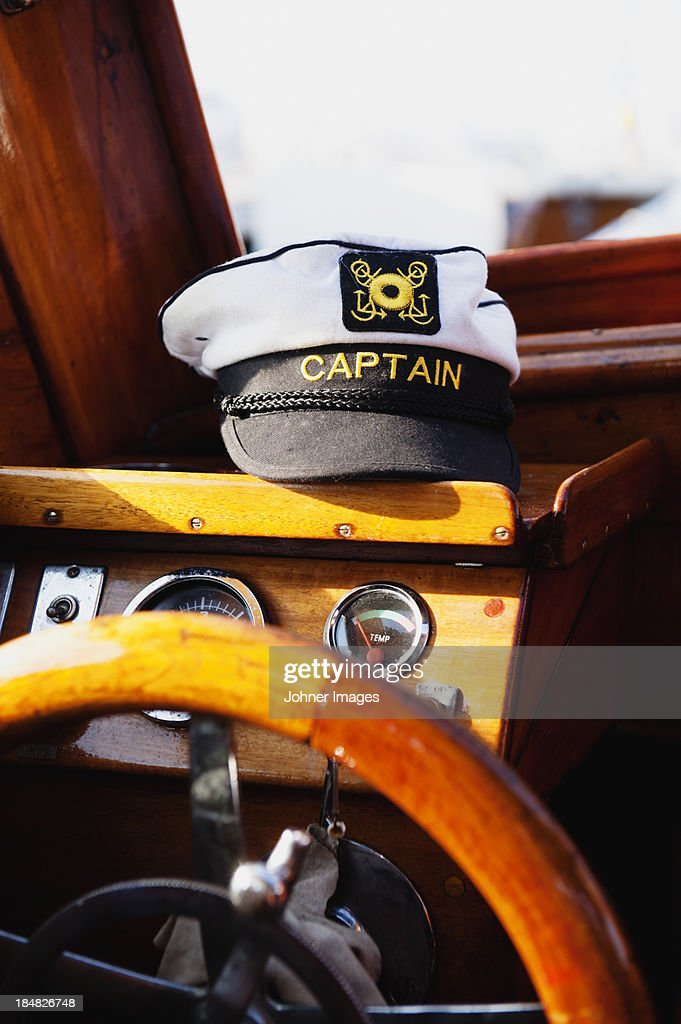 Steering wheel and captains hat in boat : Stock Photo