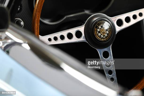 A steering wheel sits inside a battery version of Jaguar's iconic EType roadster automobile on display at the annual tech fair of Tata Motors Ltd's...
