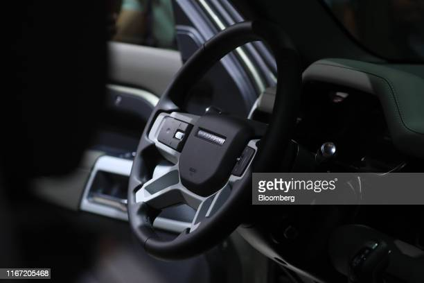 A steering wheel sits inside a new Land Rover Defender sports utility vehicle manufactured by Jaguar Land Rover Plc on the opening day of the IAA...