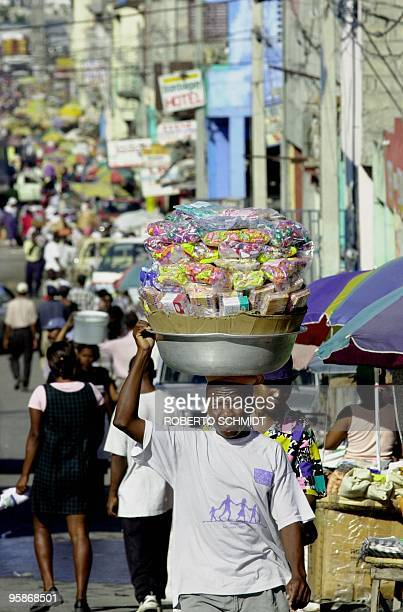 A steet salesman balances his merchandise on his head as he makes his way through a crowded street in downtown PortAuPrince 24 November 2000 Experts...