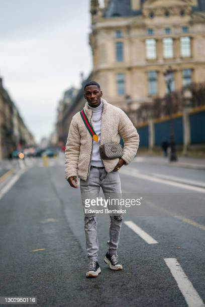 """Steevy Mbala aka """"sao.cara"""" wears a white turtleneck pullover from Boohoo, a chain necklace, a white fluffy coat from Boohoo, a Gucci crossbody bag,..."""