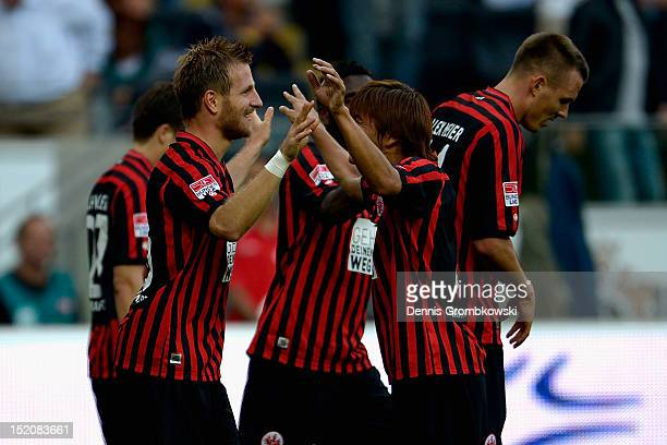 Stefan Aigner of Frankfurt celebrates with teammate Takashi Inui after scoring his team's third goal during the Bundesliga match between Eintracht...
