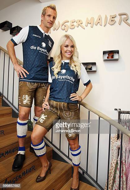 Stefan Aigner of TSV 1860 and Denise Cotte pose with traditional Bavarian lederhosen during the team fitting at the Angermeier store on September 7...
