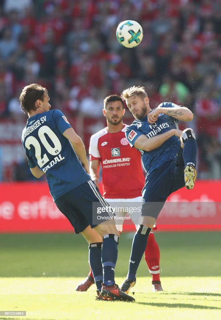 Stefan Bell of Mainz (C) challenges Aaron Hunt of Hamburger SV (R) during the Bundesliga match between 1. FSV Mainz 05 and Hamburger SV at Opel Arena on October 14, 2017 in Mainz, Germany.