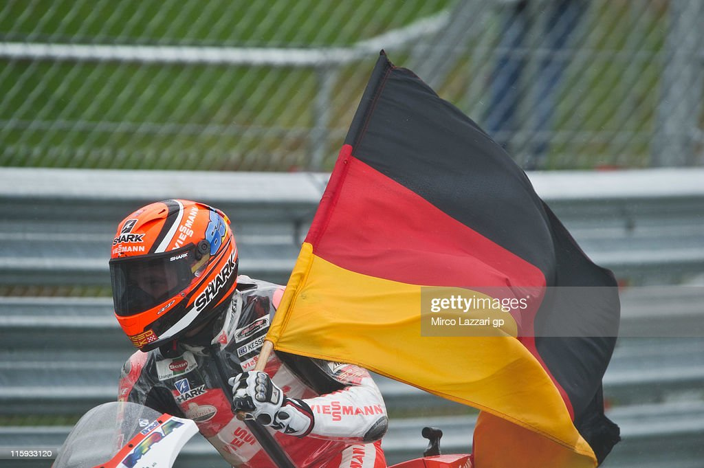 Stefan Bradl of Germany and Viessmann Kiefer Racing celebrates the victory with the flag at the end of the Moto2 race of MotoGp Of Great Britain at Silverstone Circuit on June 12, 2011 in Northampton, England.