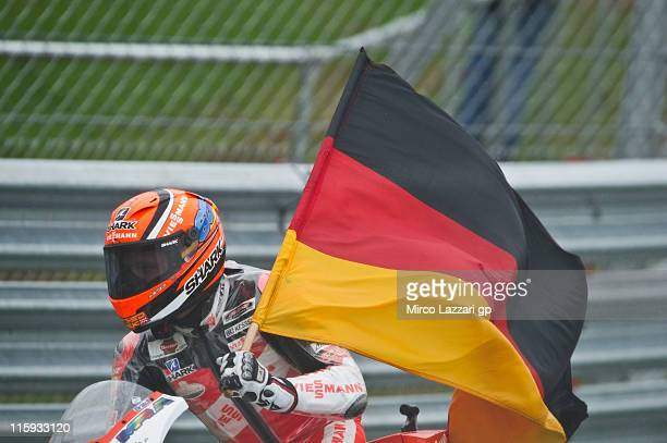 Stefan Bradl of Germany and Viessmann Kiefer Racing celebrates the victory with the flag at the end of the Moto2 race of MotoGp Of Great Britain at...