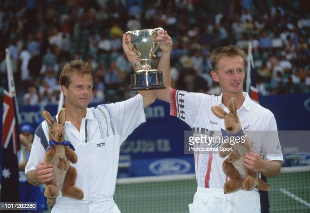 Stefan Edberg of Sweden and Petr Korda of the Czech Republic lift the trophy after defeating Sebastien Lareau of France and Alex O'Brien of the USA...