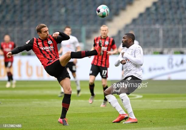 Stefan Ilsanker of Eintracht Frankfurt is challenged by Marcus Thuram of Borussia Moenchengladbach during the Bundesliga match between Borussia...